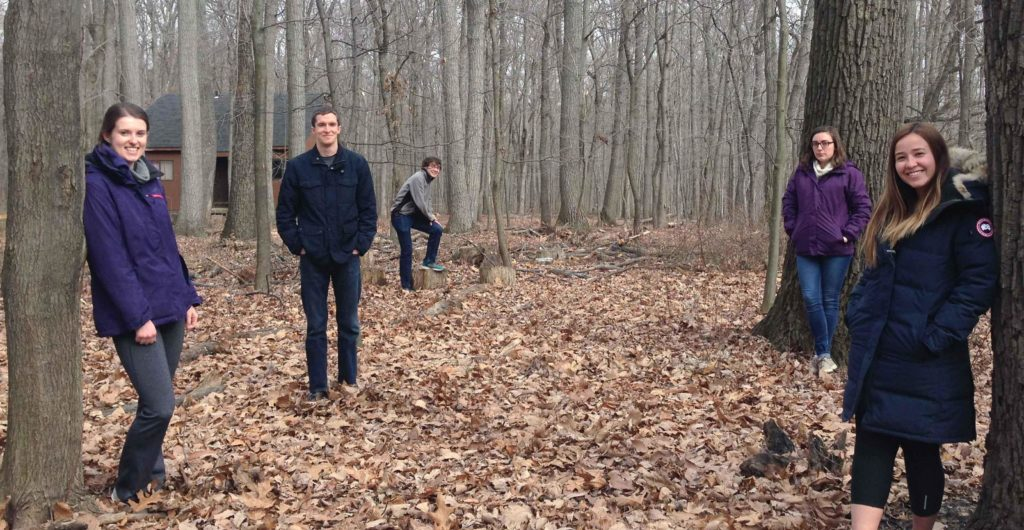 Five students standing among the trees at the Contemplative Center in the fall
