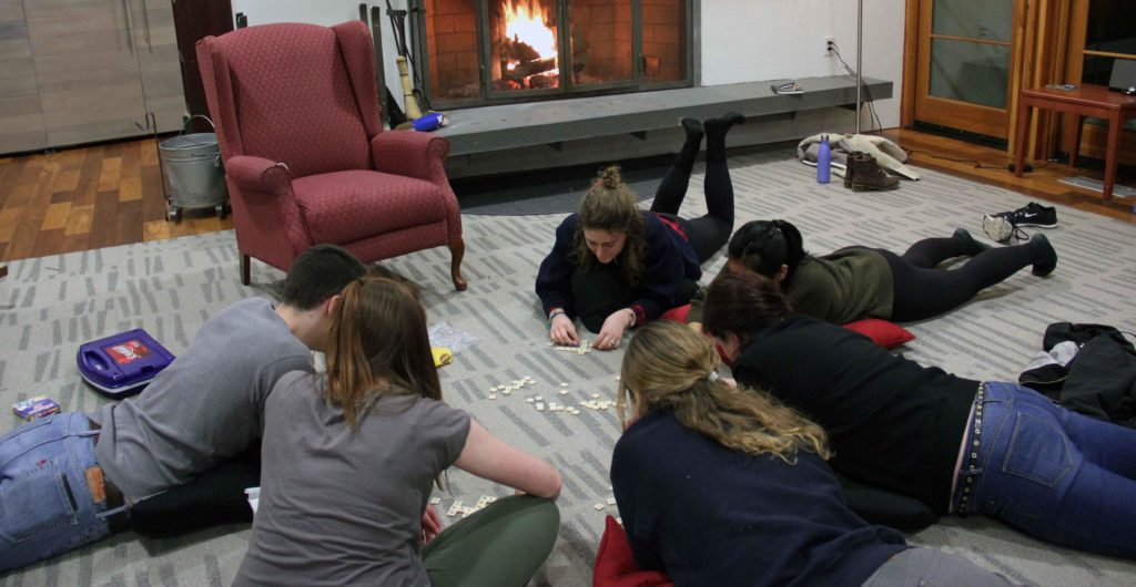 group of students laying on the floor playing scrabble