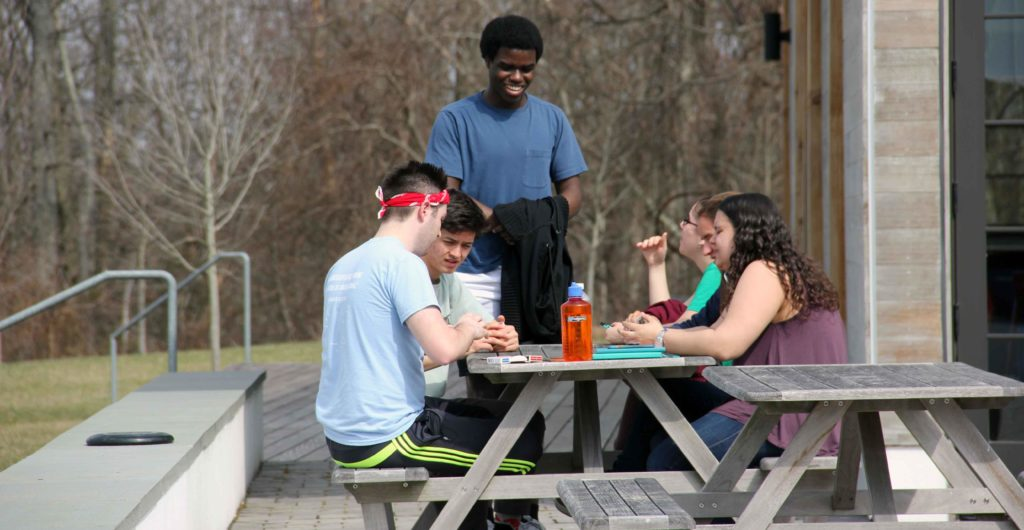 Five students at a picnic table playing cards