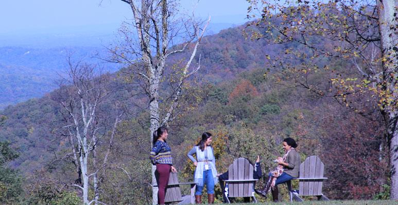 Four women gathered outdoors on Adirondack chairs