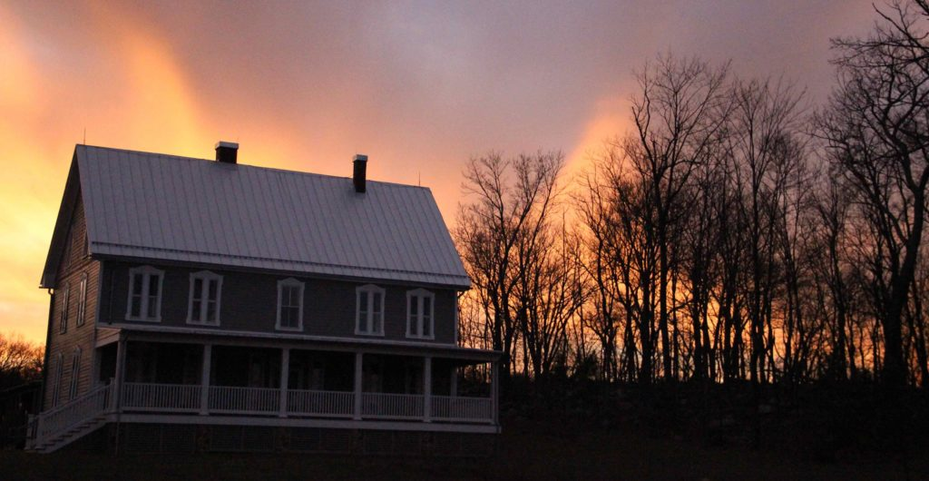 The house at the Contemplative Center with a glowing sunset