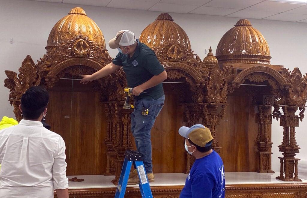 Brahmachari and carpenters installing a shrine